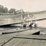Jon G. Kloechler and an unidentified man standing in the water near a slipway in front of a Wright Model B Flyer fitted with twin pontoons.