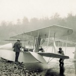 Orville Wright and others watch two men turning propellers to start the engine of the Wright Model G Aeroboat on the shore of the Miami River.
