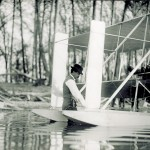 Orville Wright standing in the Miami River between the pontoons of a Wright Model CH Flyer in the summer of 1913. Two unidentified men sit in the seats of the Flyer.