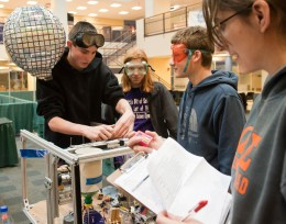 "The ""Mission Possible"" event requires participants to link many simple machines together into a large, Rube Goldberg-like device designed to release a helium balloon bearing the team's name."