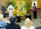 Photo of the tea mistress, wearing a kimono, in front of an audience.