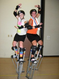 Photo of Tiffany Fridely and her friend back-to-back standing on stilts.
