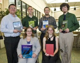 Photo of six students, each holding a book.