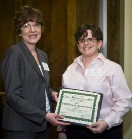 Photo of Friends of the Libraries' Board President Ellen Reinsch Friese presenting the award certificate to Gina Marie Giardina.