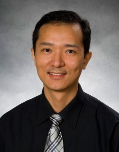Photo of Haibo Dong, Ph.D., Wright State assistant professor of mechanical and materials engineering holding two insects, which some of his micro air vehicle designs are based on.