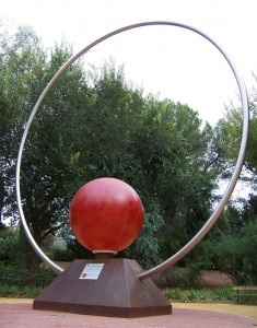 Photo of a large monument with a red spherical sun in the center of a giant steel ring.