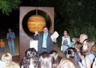 Photo of Dr. Cambronero speaking to a group of children in front of the sculpture of Jupiter.