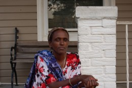 Photo of African refugee sitting on a front stoop of a home in Dayton during a block party.