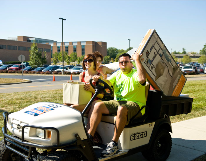 Photo of a volunteer taking a student to her building on a golf cart.