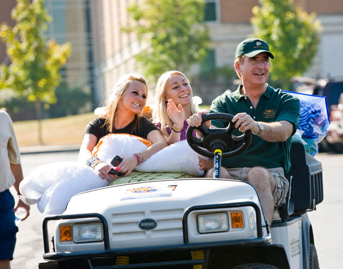 Photo of Provost Angle driving two students on a golf cart.