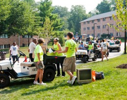 Photo of volunteers helping families move freshmen into the dorms.