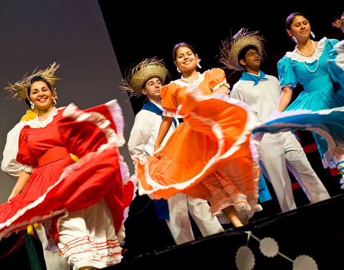 Photo of three female dances in Mexican dresses.