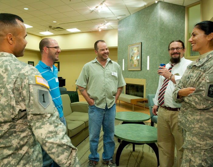 Photo of five people talking. Two are in military uniform.