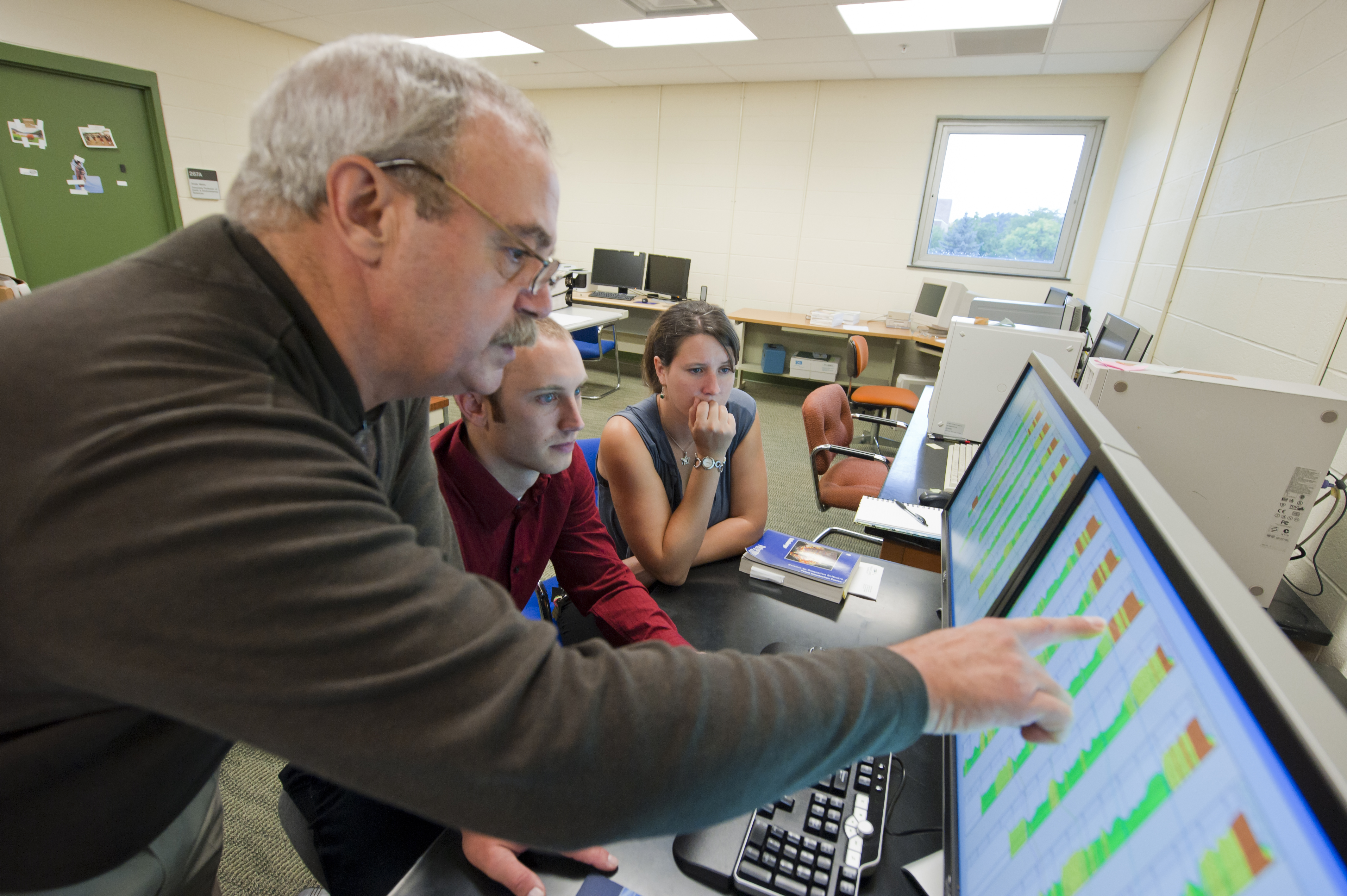 Photo of Ernest Hauser, Ph.D., showing students the benefits of the new software.