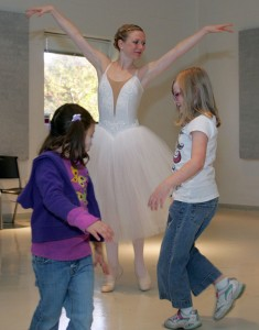 Photo of a student dressed as a ballerina teaching two young girls to dance.