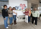 Photo of board members and volunteers from FLOC (For Love of Children) pose outside the Toy Cottage located in downtown Dayton which serves Montgomery County Children Services.