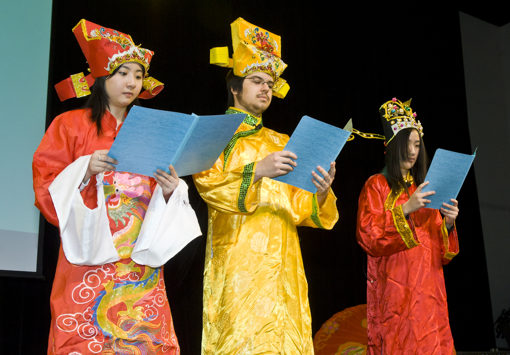 Photo of three students dressed in Asian garb on stage giving the report of the year for the World, the U.S. and Wright State.