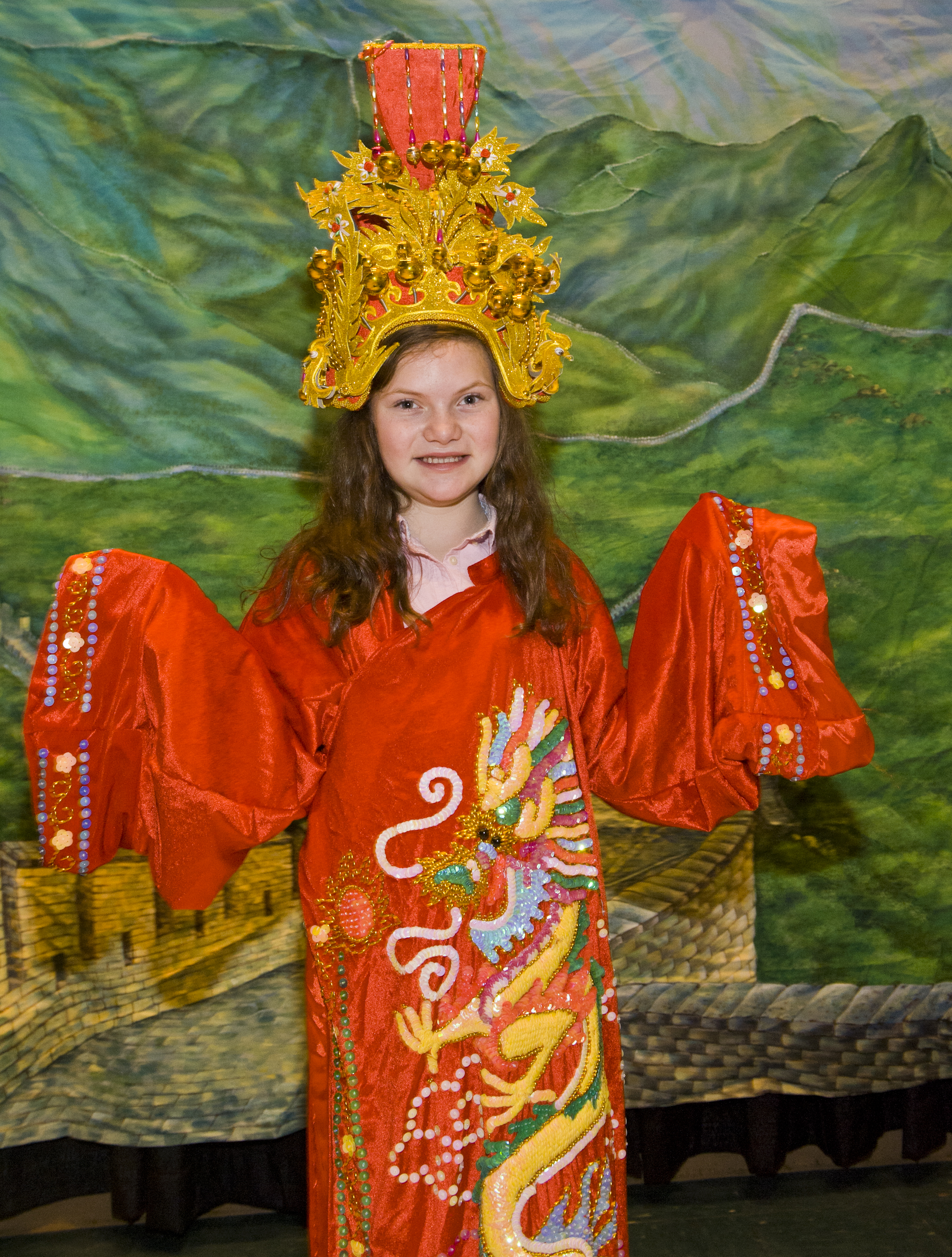Photo of young girl wearing a decroative robe with a dragon on it.
