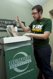 Photo of student Dan Baker recycling some paper in Allyn Hall.