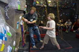 Photo of local elementary student getting a climbing lesson at the Wright State climbing wall.