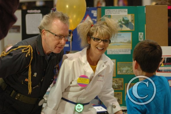 Photo of two adults and a student at the Invention Convention