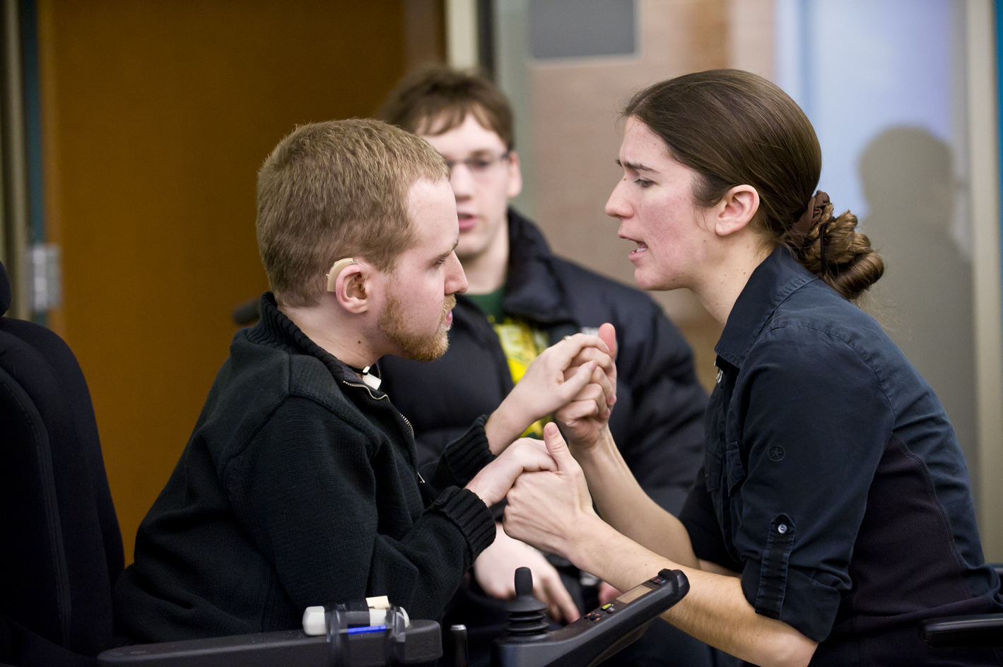 Photo of Zach Holler talking with a personal assistant.
