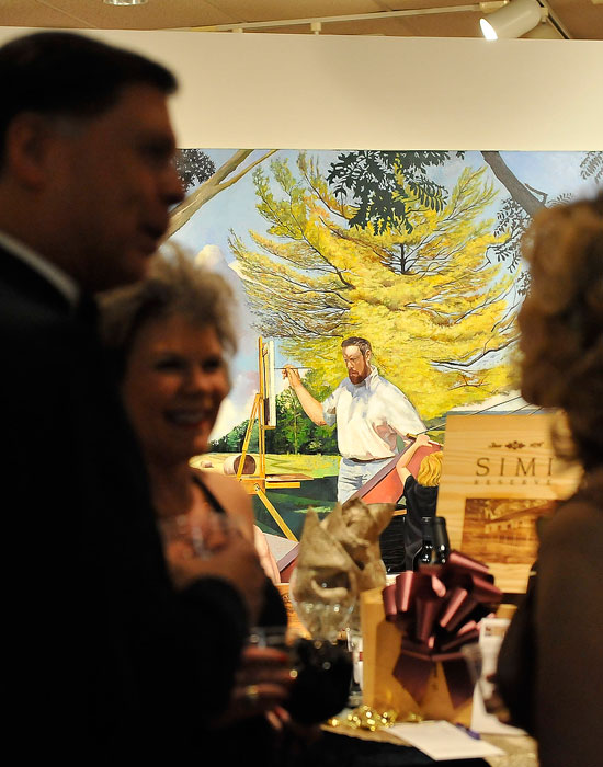 Photo of patrons in the art gallery with a painting