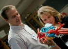 Photo of Wright State professor and a young girl examining a model of a heart.