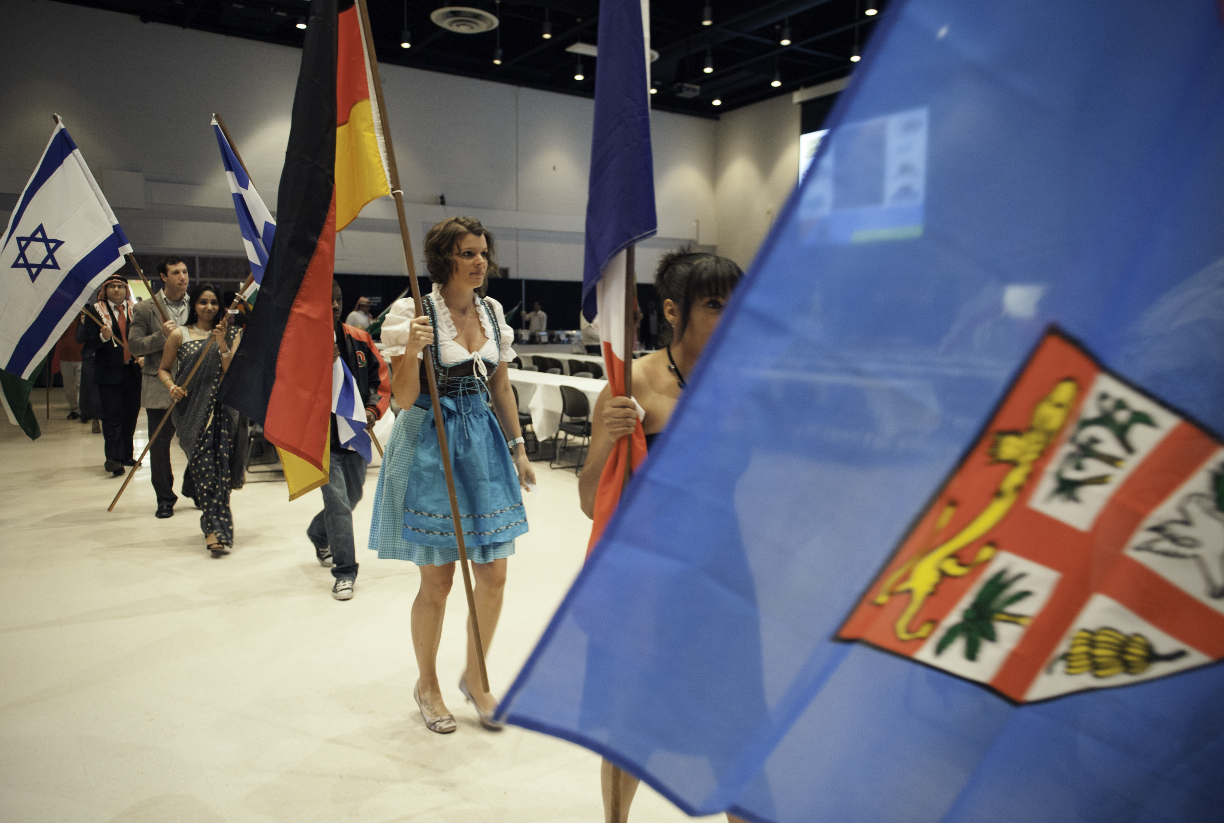 Photo of students parading through the Apoillo Room at the Srtudent Union with flags from their home country.