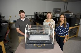Photo of Biomedical engineering students Jessica Hernandez (right), Joanna Newton and Jacob Durdel displayimg the incubator they designed and built. The incubator and others will be sent to the Congo in Africa.