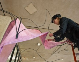 Photo of Megan Dooley-Smallwood sewing on the petals of her sculpture.