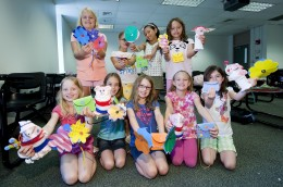 Photo of several pre-college students showing off their creations from their Sewing Creations class.