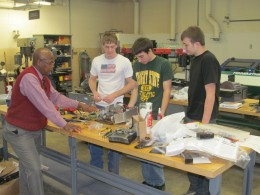 Photo of Ruby Mawasha, Jordon Coffman, John Neifert and Jared Runyon working on their battle bot Crimson Chaos.
