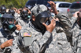 Photo of U.S. Army Capt. Tejdeep Singh Rattan putting on a gas mask