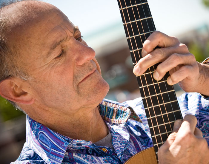 Photo of Alan Dine playing the guitar