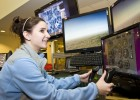 Photo of Courtney Banatta trying a flight simulator at Wright Brothers Day.