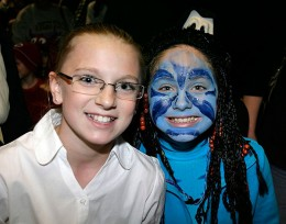 Photo of two kids, one with face painted blue as a creature from Avatar.
