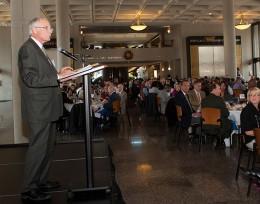 President Hopkins speaking at a podium.