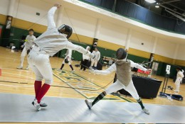 Photo of two people competing in a fencining tournament at the Wright State University Nutter Center.