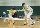 Photo of two people competing in a fencining tournament at Wright State University's Nutter Center.