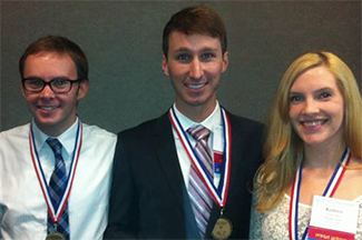 Photo of three students with medals