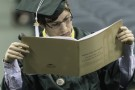 A graduate searches for his name in the Commencement program.