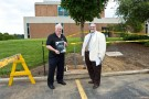 Jim Halderman, left, and Scott Moniaci, associate director of engineering and construction, stand next to the charging-station site outside Allyn Hall.