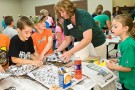 Stacey Hundley helps elementary school students make volcanoes