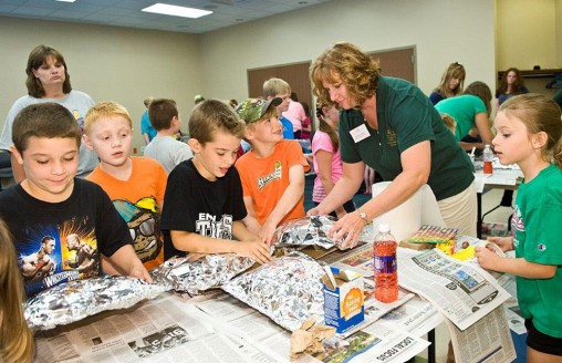 Stacey Hundley helps elementary school students make volcanoes