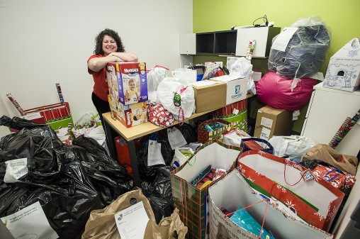 Annette McCoy, coordinator of the holiday gift program poses with the 2014 haul of toys from the Wright State community.