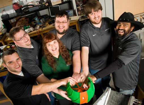 Robotics team members with 3-D wheel