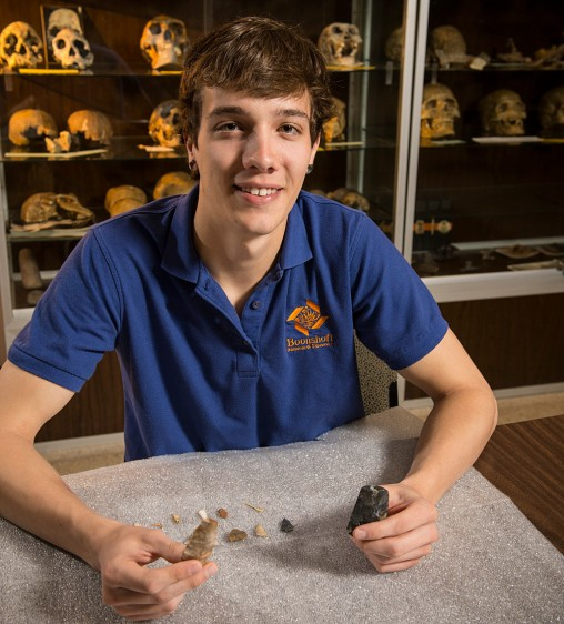 Tyler Heneghan holding arrowheads and artifacts