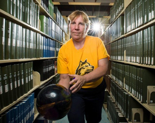 Mandy Wilson with bowling ball in library stacks