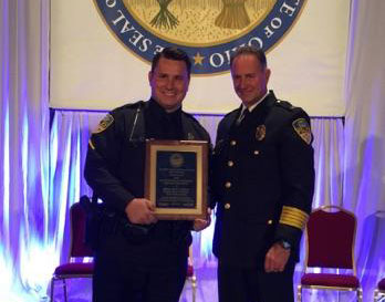 (L-R) Wright State police officer Kurt Holden and Police Chief David Finnie pose for a picture with the award at the Attorney General's Law Enforcement Conference Oct. 9, 2015.